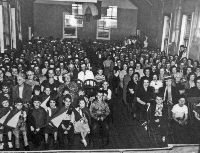 The audience for an elementary stage production in 1950.  Note the basketball hoop.