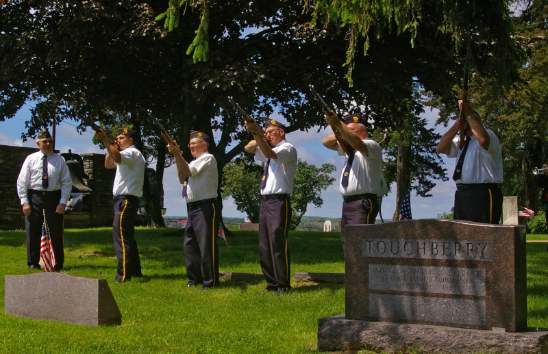 The Post Honor Guard fires a salute to honor the fallen.