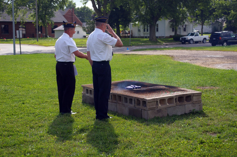 Post commander Marv Peters and Scott Droessler oversee retirement of the first flag.